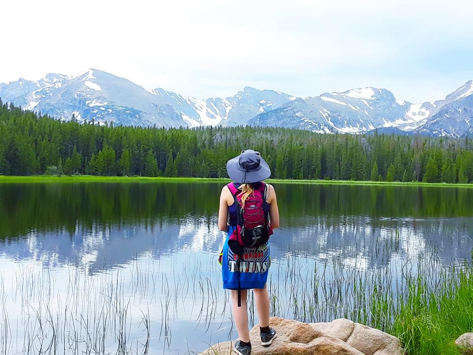 Photo of a Beautiful Woman Standing Beside Crystal Clear Bierstadt Lake, One of the Best Estes Park Hikes.